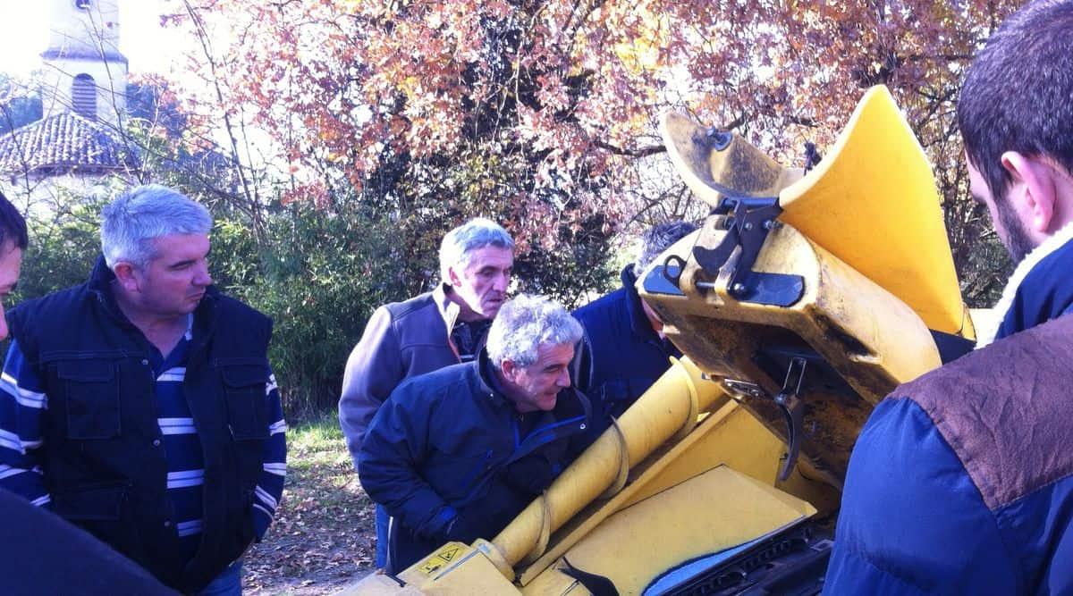 Nicolas Thibaud explique aux chauffeurs, au pied d'une moissonneuse-batteuse, comment régler la machine pour récolter de manière efficace.